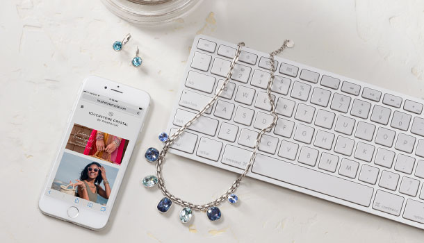 Computer keyboard with blue Basketweave Necklace and mobile phone displaying Touchstone Crystal Website